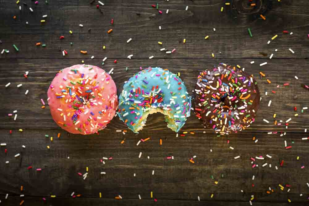 Three donuts with sprinkles on a wooden table, one is bitten