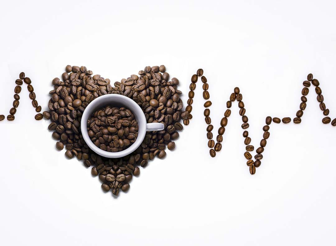 A cup with coffee beans with an Electrocardiagram made out of coffee beans